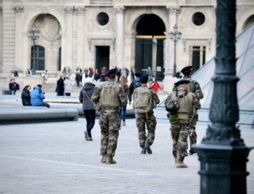 Armed Counter Terrorism officers in uniform walk away from the camera towards a capital building
