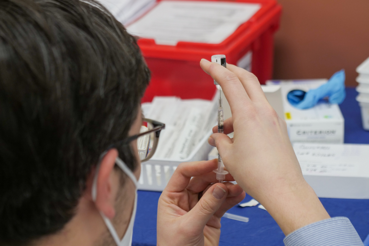 Doctor at a secure vaccine site is preparing a vaccine for use.