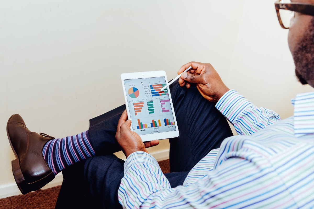 man wearing office clothes holding an ipad reviewing reports with graphs and bar charts