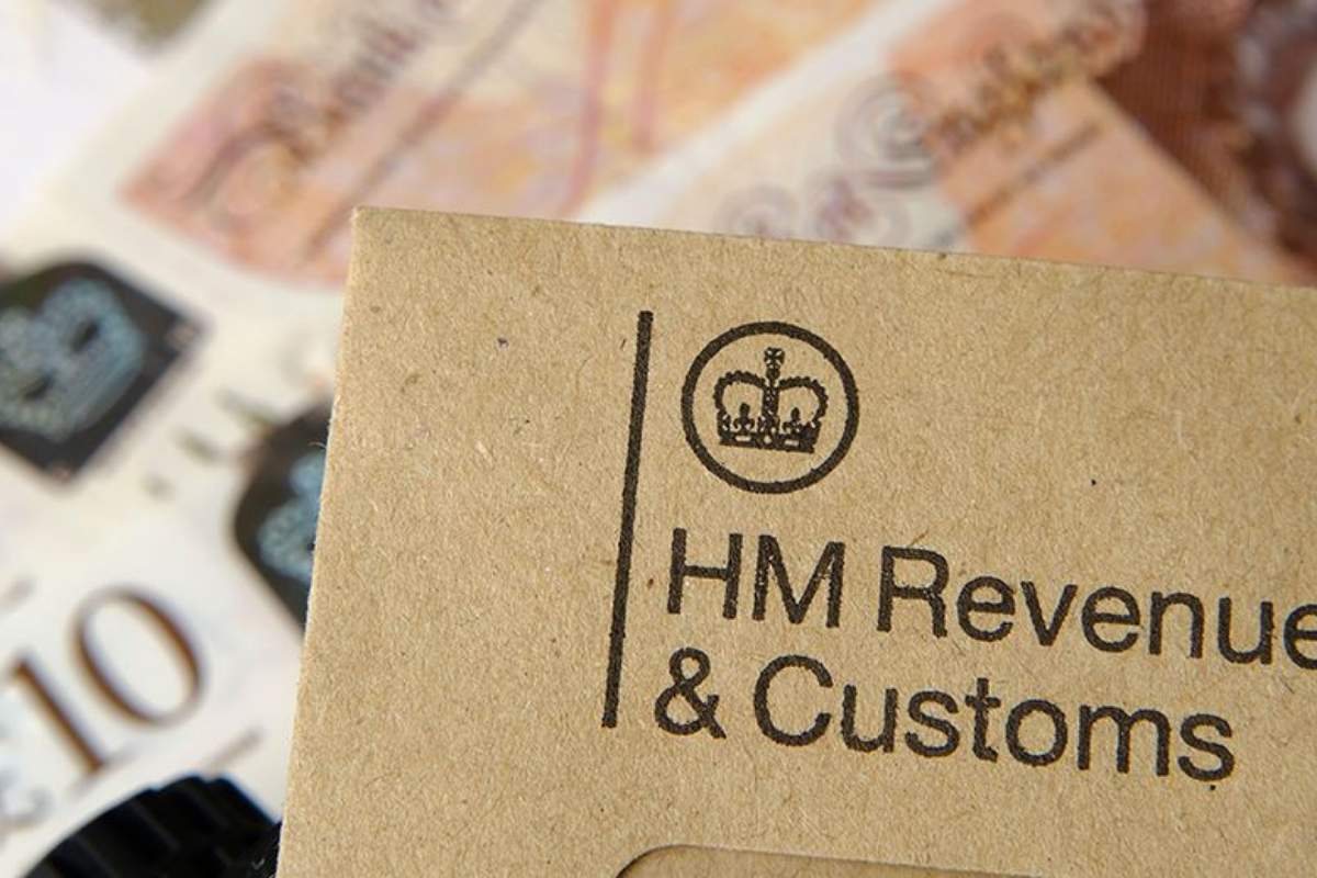 Top left corner of a brown envelope with the HMRC logo. You can see multiple ten pound notes splayed out in the background