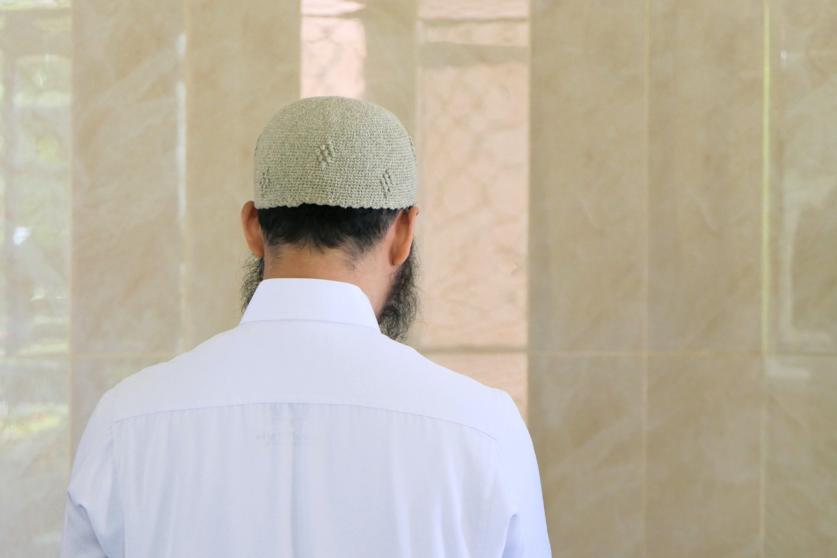 a muslim gentleman faces the wall of a mosque for prayer during ramadan