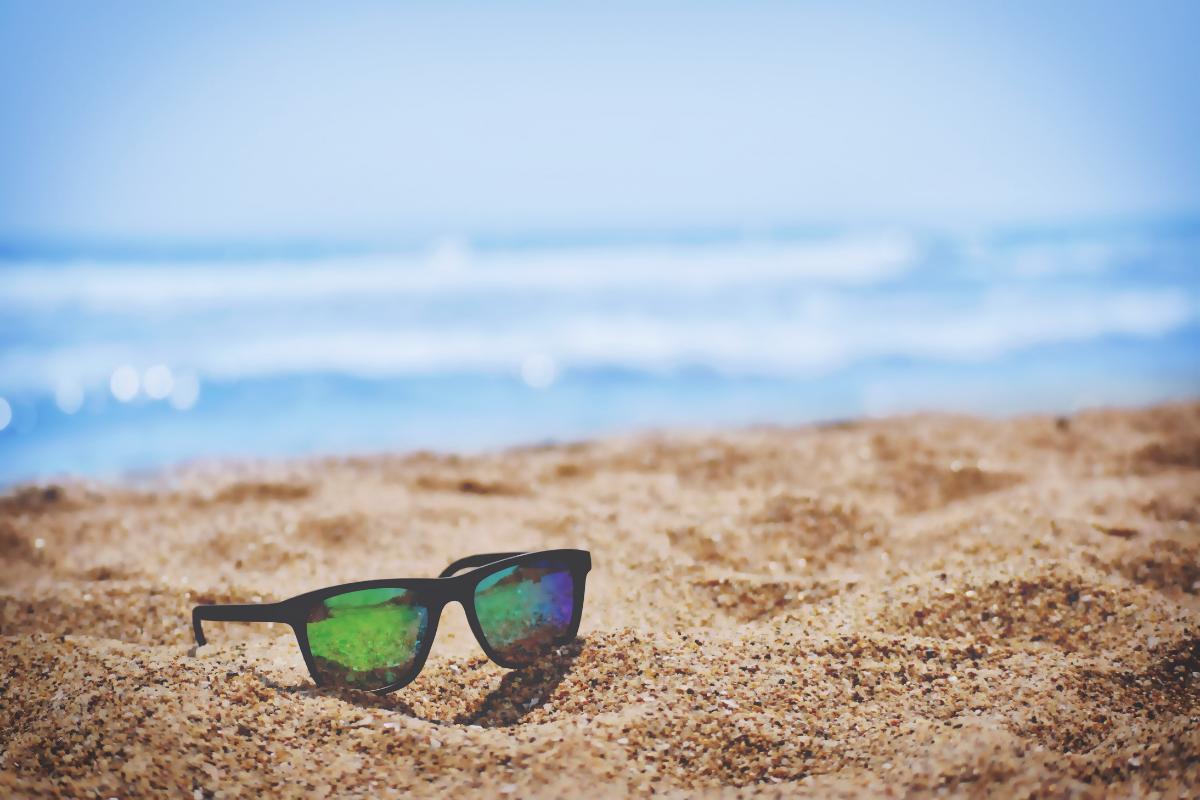 sunglasses on a sunny beach with sea behind